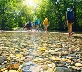 foto of bow-legged  - Group of backpackers fording cold river - JPG