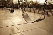 stock photo of obese children  - Swings at an empty playground signifying lost youth or lost generation - JPG