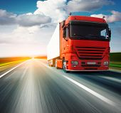 image of trucks  - Red truck on blurry asphalt road over blue cloudy sky background - JPG