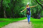picture of long distance  - Young woman walking on path in city park - JPG
