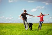 stock photo of male female  - Young happy pair running on green meadow with a dog - JPG