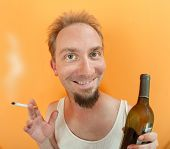 image of wife-beater  - Caucasian man holding a cigarette and a alcohol bottle with a big smile - JPG