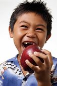 foto of toothless smile  - boy with missing front teeth about to bite an apple - JPG