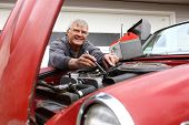 image of senior men  - Senior man working on classic car - JPG