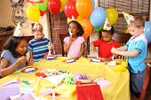 foto of birthday party  - Group of children eating cake at birthday party - JPG