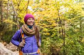 Happy Asian woman hiking in autumn forest nature walking on trail path. Hiker girl with backpack, ha poster