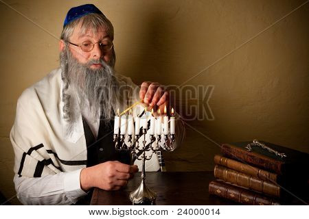 Old jewish man with beard lighting candles for hannukah