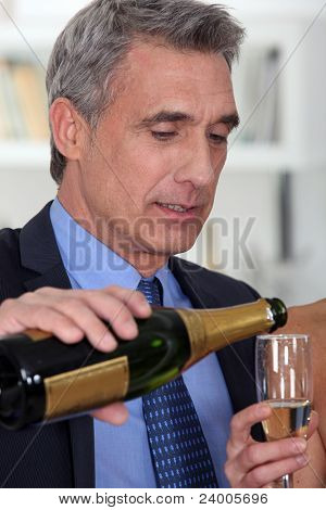 A mature man pouring champagne.