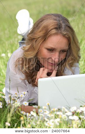 Relaxed woman lying in a field of daisies using her laptop