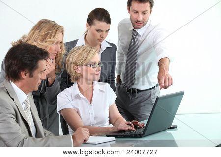 Business team sitting around a laptop computer