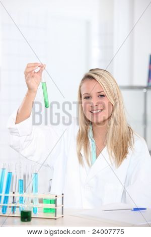female biologist in laboratory holding test tube
