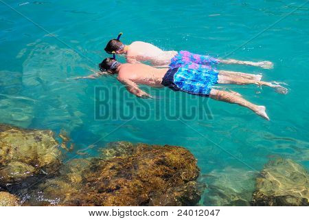 Two tourists snorkeling in clear sea water.