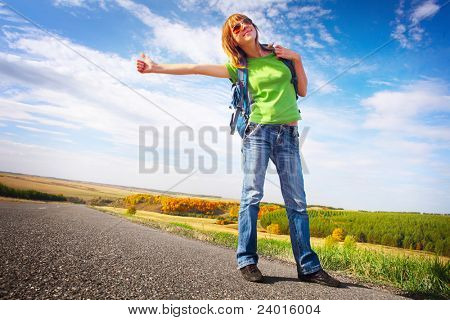 Young smiling woman in glasses and with backpack hitch hiking on an asphalt road