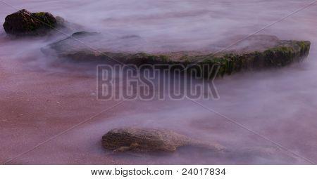 Hazy Stones At Sea Shore Background
