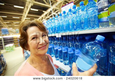 Image of mature customer holds bottle of pure water
