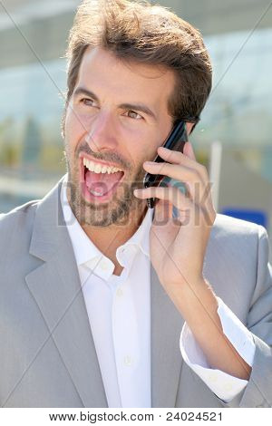 Portrait of cheerful businessman talking on mobile phone