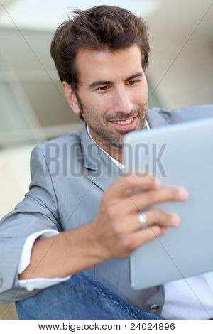 Portrait of smiling man using electronic tablet outside
