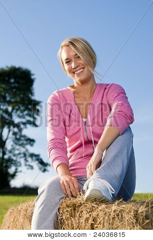 Sportive Young Woman Relax On Bales Sunset
