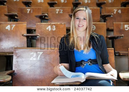 Portrait of young college girl studying at university hall
