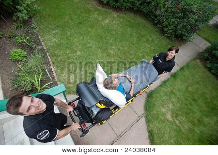 Above view of an emergency medical team pushing stretcher with senior woman in a residential area.
