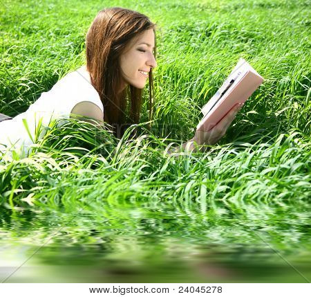beautiful woman lays on green field and reads book