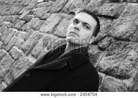 Mystery Man Leaning Against Stone Wall