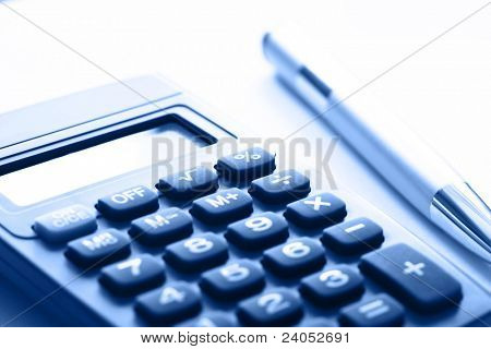 Calculator and pen in blue color, shallow focus