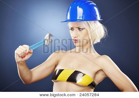 Attractive Girl With Construction Helmet And Adjustable Wrench.