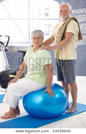 Smiling old couple relaxing after workout, man giving massage to woman.?