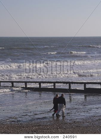 Middle Age Couple Strolling On Beach