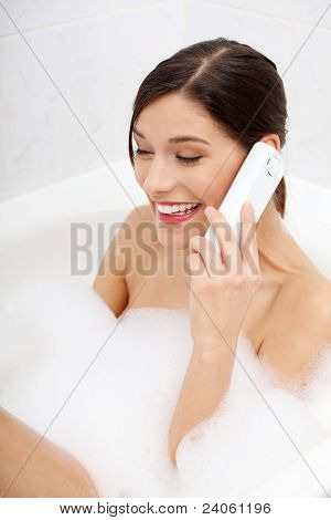 Beautiful young woman talking by wireless phone while taking a bath