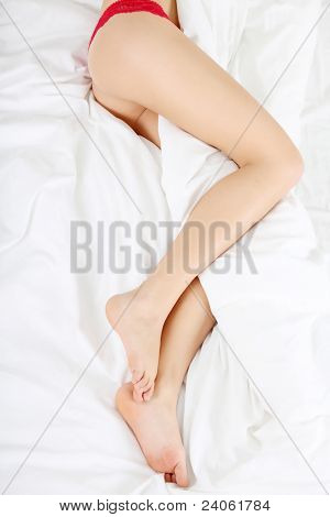 Woman legs on the bed