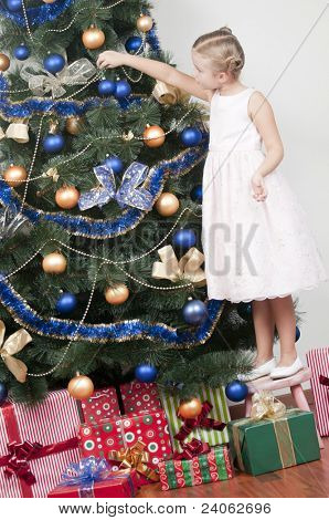 Christmas time - cute girl decorating a Christmas tree