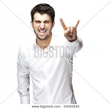 Retrato de hombre joven haciendo un símbolo del rock and roll sobre fondo blanco