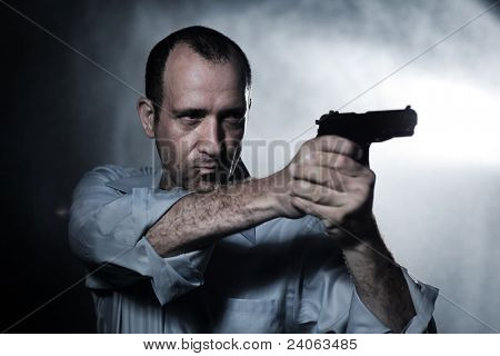 Man aiming pistol gun at night. Closeup.