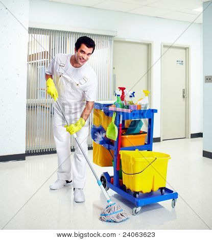 Young professional cleaner washing the floor. Janitor cart.
