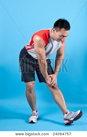Young fit man doing hamstring stretch