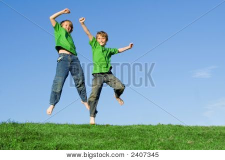 Happy Smiling Children Jumping Outdoors
