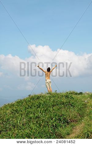 Meeting Of The Sky. The Man On High Mountain With The Hands Lifted Above, On A Background Of Blue Sk