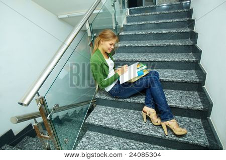 Photo of pretty girl sitting on stairs and making notes in copybook