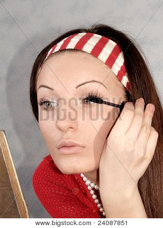 A girl paints the lashes with a brush