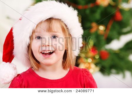 Lovely preschooler in Santa hat, smiling