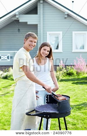 Attractive young couple makes a barbecue