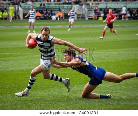 MELBOURNE - SEPTEMBER 24 : James Kelly (L) evades a tackle from Andrew Embley during Geelong's preliminary final win over West Coast on September 24, 2011 in Melbourne, Australia.