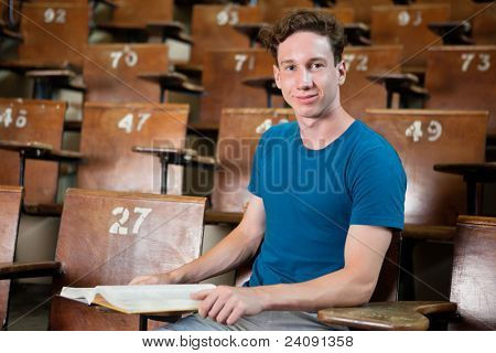 Portrait of young university student sitting in lecture hall