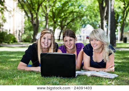 Portrait of three students working on laptop on campus ground