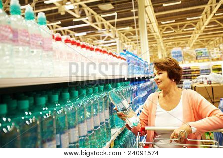 Image of mature customer choosing water from big assortment in a shop
