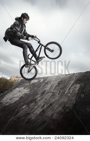 Jovem homem pulando e andando em uma bicicleta de BMX em uma rampa sobre fundo de céu nublado