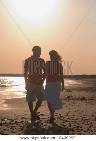 Young Couple Walking On Sand.