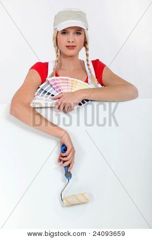 Female decorator with a color chart and roller